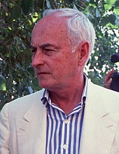 An elderly Caucasian man with white hair wearing a white jacket and a white-and-blue-striped shirt.