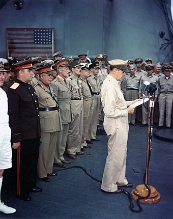 MacArthur at surrender ceremony. The flag flown by Perry is visible in the background. Japanese-surrender-mac-arthur-speaking-ac02716.jpg