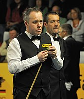 John Higgins stands holding his cue in his right hand while he chalks it with his left hand.