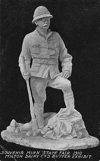 Photograph of a butter sculpture of Teddy Roosevelt by John K. Daniels at the 1910 Minnesota State Fair, depicting Roosevelt resting his left leg atop the carcass of a lion he ostensibly shot while wearing a safari hunter outfit
