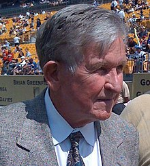 A head shot of an older man wearing a gray suit with stadium seating in the background.