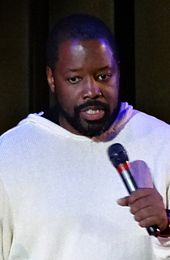 A man wearing a white/grey shirt is talking into a microphone.