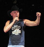 A man in a cowboy hat and dark singlet holding a microphone.