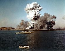 A warship observes as a port explodes in the background