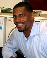 A black man wearing a blue button-down shirt sits and poses for a picture at a wooden table.