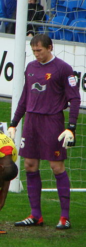 White man in sports kit standing near a goal