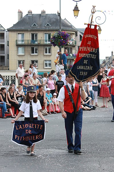 Flag carrier for the L'alouette de Pithiviers choirs during the 50th fêtes à Jean in Château-Thierry, France.