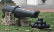 A long 19th-century cannon with a stack of cannon balls in front of it, sitting on a lush green lawn.