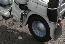 The image shows the port side (left side when facing forward) of a Lambretta Model C. The wheel and the lug nut are visible but there is no visible connection between the wheel and the rest of the scooter.