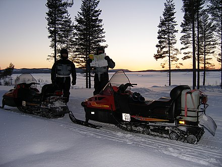 Two Swedish snow mobiles with license plates attached to the side of the vehicles.