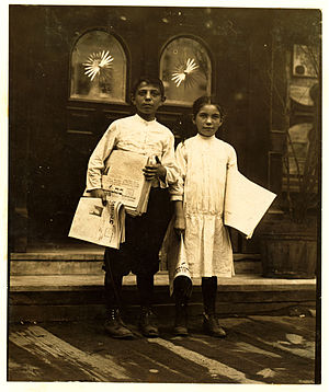 Newspaper hawker - A newsgirl and boy selling papers outside saloon entrances in New York, 1910