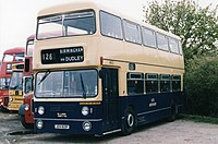front  quarter view of double-decker bus painted dark blue on the bottom and cream at the top