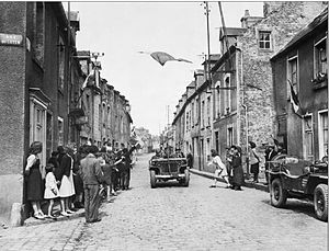 Battle of Carentan - US 7th corps jeep passes under the French flag as civilians thank the Americans after liberating the town.