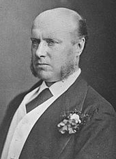 A balding man with long sideburns, wearing a suit with a buttonhole carnation