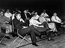 A group of men in shirtsleeves sitting on folding chairs