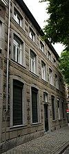 foto van Huis met brede lijstgevel, voorzien van hardstenen segmentboogomramingen en een ingang met gebeeldhouwde sluitsteen.