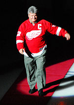Marcel Dionne walking down a red carpet on ice while wearing a Red Wings jersey