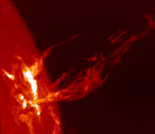 At left is a section of a red disk with an irregular bright region. Streams of red plasma trail off to the right.