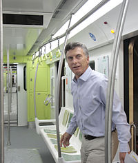 Macri walking into a new, colorful subway car
