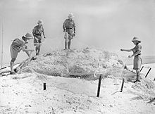 Four soldiers standing around an obscured gun position.