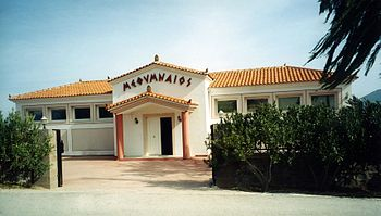 Methymneos winery. Methymneos is spelled in Greek letters above the building's awning-covered, opened door.