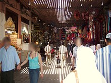 A photograph of a busy passageway leading from the foreground to the background contains people walking in both directions illuminated by elongated slats of light.