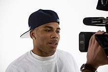 A man in front of a handheld video camera, wearing a white t-shirt and his cap backwards