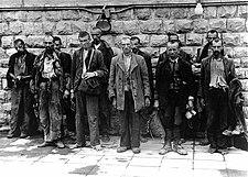 Useat miehet seisovat tiiliseinän edessä.