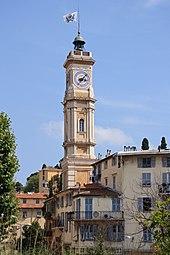 Vue en ville d'une tour avec une horloge. Sur le toit de la tour se trouve une cloche surmontée d'un drapeau.