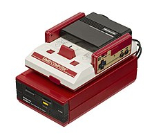 A white and red Famicom unit sits atop a candy red Famicom Disk System unit with black insertable disk drive. Two rectangular controllers, each with a D-pad and two black buttons, fit into the Famicom.