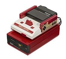 Uma unidade Famicom branca e vermelha fica em cima de uma unidade Famicom Disk System vermelho doce com uma unidade de disco preta inserível.  Dois controladores retangulares, cada um com um D-pad e dois botões pretos, se encaixam no Famicom.