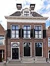 foto van Fors pand met versierde kroonlijst met U-vormig zadeldak onder dwarsdak met twee hoekschoorstenen en dakkapel en groot venster aan achterzijde met uitzicht op zee
