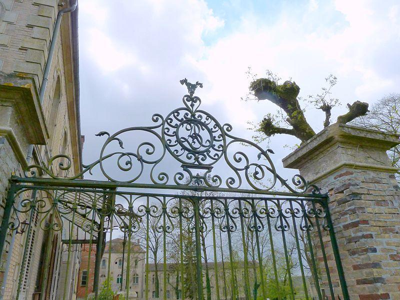 Noyers-Auzécourt 55 Maison du Val grille du parc de l'ancienne fromagerie Louis Bailleux, sur laquelle on peut voir son monogramme: les initiales LBC entrelacées.