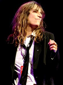 A photograph of Patti Smith looking to the side of the camera while performing onstage