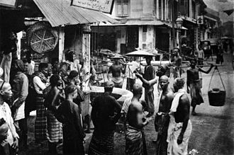 Singaporeans - Men of various races- Chinese, Malay, and Indian gather at a street corner in Singapore, circa 1900.