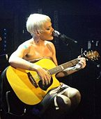 A woman with short blonde hair singing with her microphone while playing a guiar