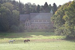A photograph of St Margaret's Church, surrounded by trees, with a grass field in the foreground