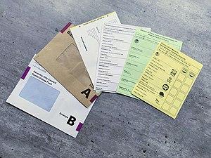 Zwei Umschläge, ein Briefwahlzettel und drei verschiedenfarbige Stimmzettel auf einem Tisch