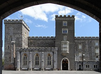 Powderham Castle - Powderham Castle, west front, viewed from under the Victorian gatehouse. The leftmost tower dates from 1390–1450 as does the main high central block, which originally housed a full-height great hall. The central entrance tower was built 1710–1727. The single-storey projecting room built between the two towers, with three tall gothic-style windows, is the Victorian Dining Hall.
