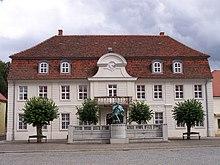 Ehemaliges Rathaus in Stavenhagen (heute Fritz-Reuter-Literaturmuseum) mit Statue Reuters (Quelle: Wikimedia)