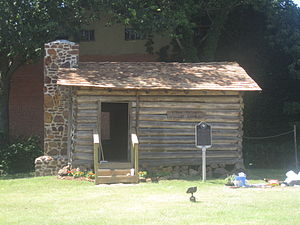 Crockett, Texas - The historic Strode-Pritchett Cabin was located to Crockett for the 1976 bicentennial. At the site is a painting of Davy Crockett by the artist Lucas Short.