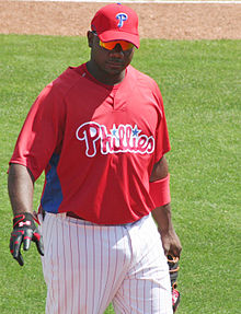 "A dark-skinned man wearing a red baseball jersey with ""Phillies"" across the chest and a red baseball cap walking on a grass field"