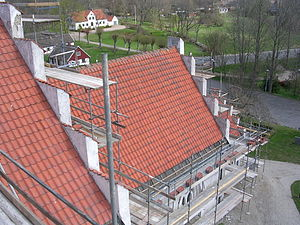 A church roof under repair with terracotta tiles