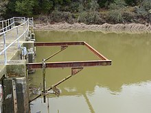 A photo showing a frame on Searsville Dam which at one time supported a diving platform