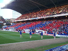 Photo of 7 cheerleaders performing on a football pitch in front of a packed stand with many on the lower tier waving red and blue flags.