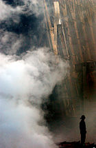 A solitary firefighter stands amid the rubble and smoke in New York City