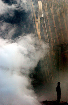 Photograph of smoke rising in front of upright steel members of a shattered building. A firefighter is visible as a dark silhouette standing still amid the smoke.