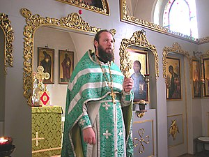 Sticharion - Russian Orthodox priest holding a blessing cross. His white sticharion is visible beneath his green vestments.