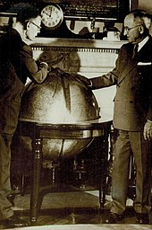 Smith (wearing glasses) and Truman lean over a large globe. A clock on the mantelpiece behind the globe indicates that it is ten o'clock.