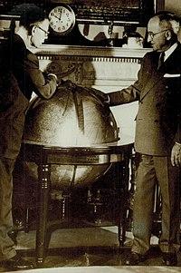 Smith (w okularach) i Truman pochylają się nad dużym globusem.  Zegar na kominku za kulą ziemską wskazuje, że jest godzina dziesiąta.